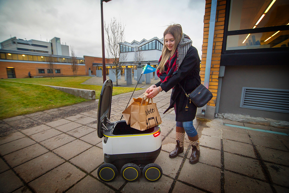A student at Tallinn University of Technology receives one of the first-ever food deliveries by a robot in Tallinn in autumn 2016. (Image: Wolt)
